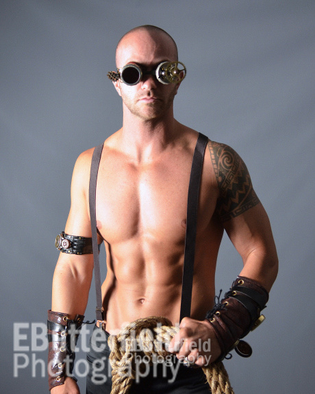 Muscular shirtless male model with tools and rope