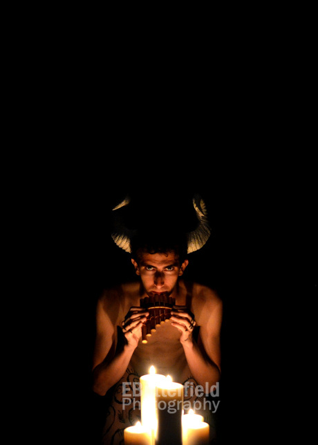 Horned god Pan with flute and candles