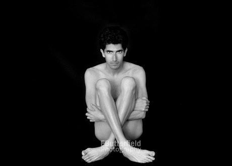Nude male sitting cross-legged; black and white photo.